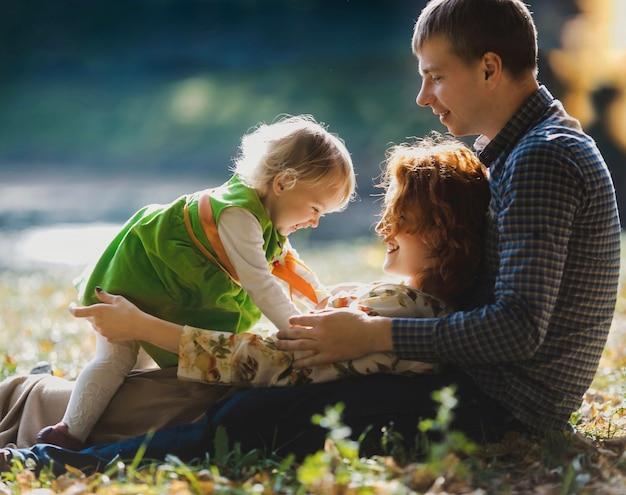 Il padre, la madre e la figlia si trovano sull'erba