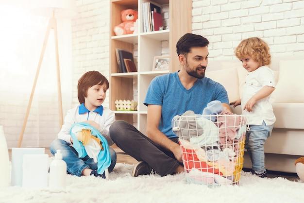 Il padre mostra ai bambini come pulire la casa.