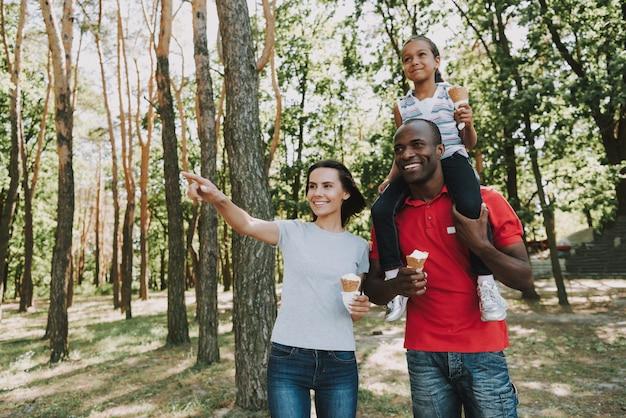 Il padre nero porta la figlia sul collo in foresta.