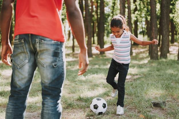 Il padre nero sta giocando a calcio con la figlia.