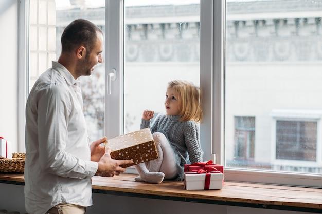 Il padre presenta il suo contenitore di regalo della figlia su natale a casa