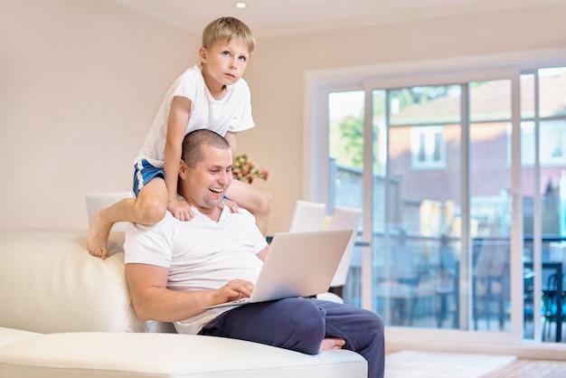 Il padre si siede sul divano, guarda il portatile e ride, il figlio si è arrampicato sul collo a papà, emozioni di gioia da ciò che ha visto, famiglia felice