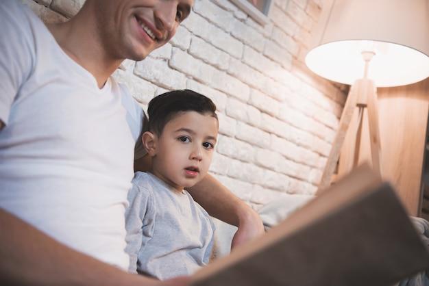 Il padre sta leggendo il libro delle fiabe a suo figlio durante la notte.