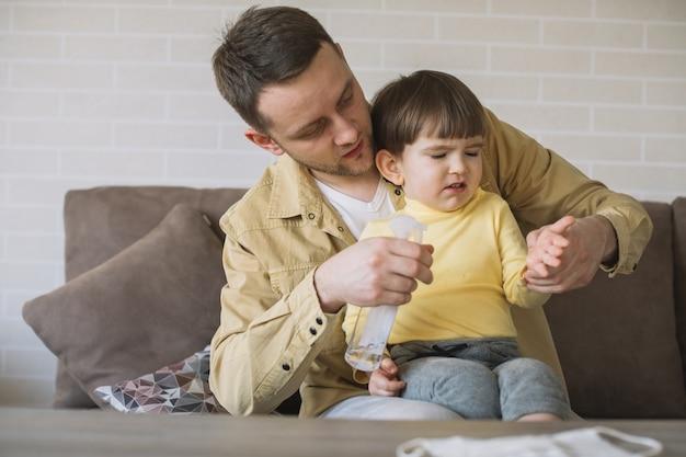Il padre usa il disinfettante per le mani sulle mani del figlio