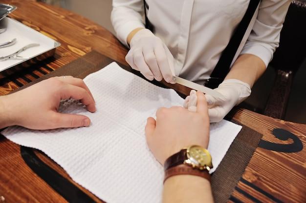 Il padrone del salone di bellezza della donna fa una manicure ad un cliente maschio