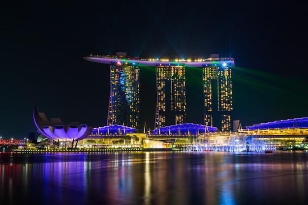 Il paesaggio urbano dell'orizzonte di singapore con la luce e l'acqua mostrano intorno alla baia del porticciolo alla notte.
