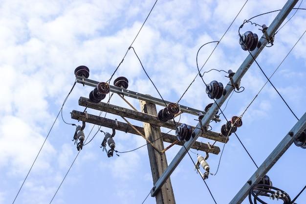 Il palo elettrico si collega ai cavi elettrici ad alta tensione su contro il cielo blu luminoso