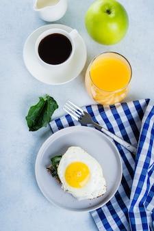 Il pane di segale tosta con gli spinaci e l'uovo fritti sulla tavola blu. concetto di cibo sano colazione.