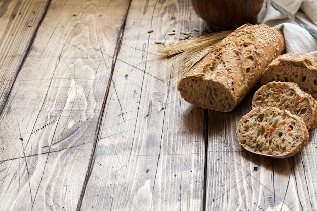 Il pane fresco con semi di girasole, semi di sesamo e lino viene tagliato a pezzi su un tagliere.