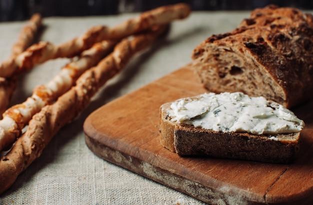 Il pane scuro si diffonde con la ricotta alle erbe in un taglio su una tavola di legno