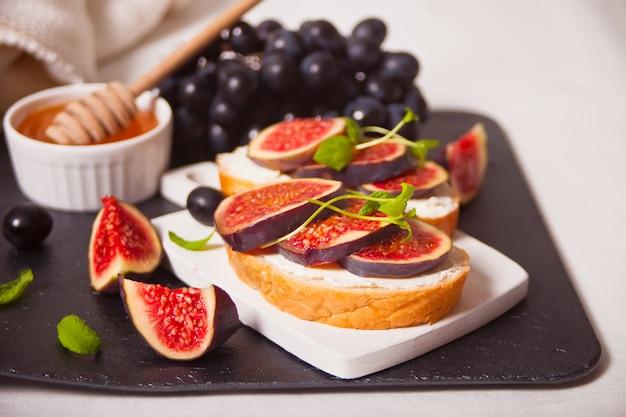 Il panino con crema di formaggio, fichi e miele è servito sul piatto grigio sul bianco. cibo salutare