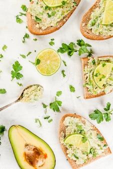 Il panino fatto in casa tosta con guacamole, lime lime e prezzemolo sul tavolo bianco, copia spazio vista dall'alto