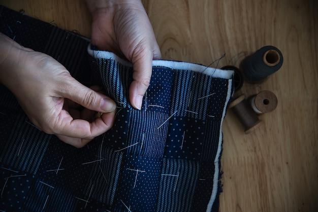 Il panno di cucito della donna dell'annata a mano con ricamo ha messo sulla tavola di legno - la gente e concetto diy fatto a mano di lavoro domestico