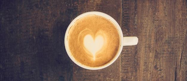 Il panorama ha sparato del caffè di arte del latte sulla tavola di legno