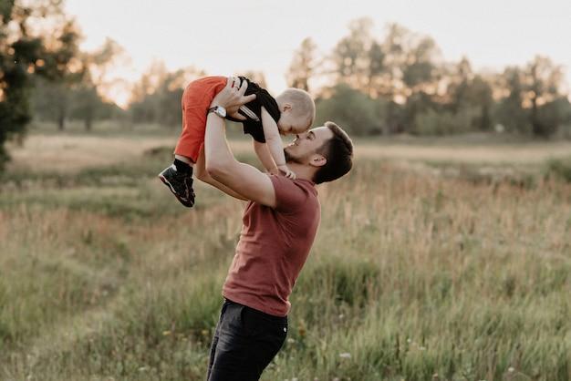 Il papà e il figlio felici sorridono e giocano nel campo al tramonto