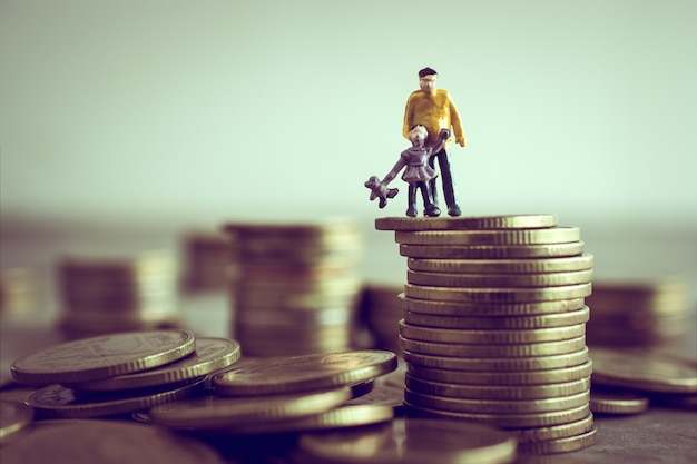 Il papà ed i bambini miniatura che stanno sopra i soldi risparmiano il concetto dei soldi.