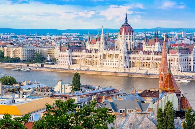 Il parlamento e la riva del fiume a budapest in ungheria durante la bella giornata di sole estivo contro il cielo blu e nuvole.