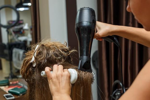 Il parrucchiere asciuga i capelli al cliente con un asciugacapelli.