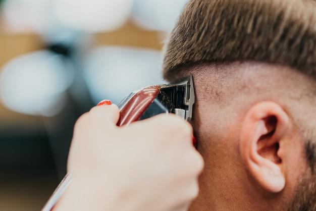 Il parrucchiere bella ragazza taglia un uomo barbuto nel salone