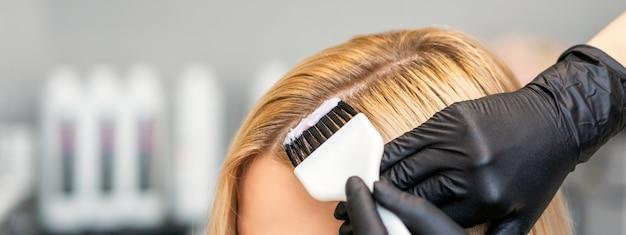 Il parrucchiere colora i capelli femminili del cliente