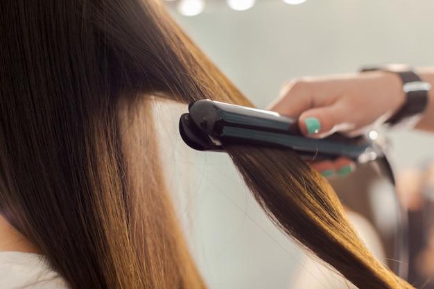 Il parrucchiere fa lo stile di capelli della donna