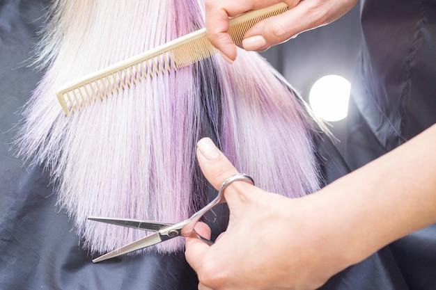 Il parrucchiere fa un taglio di capelli a una ragazza con lunghi capelli biondi. mani del parrucchiere che tengono le forbici e il pettine