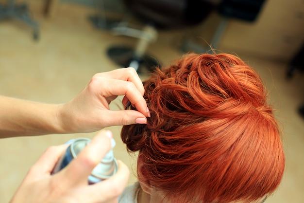 Il parrucchiere fa una bella acconciatura al salone c