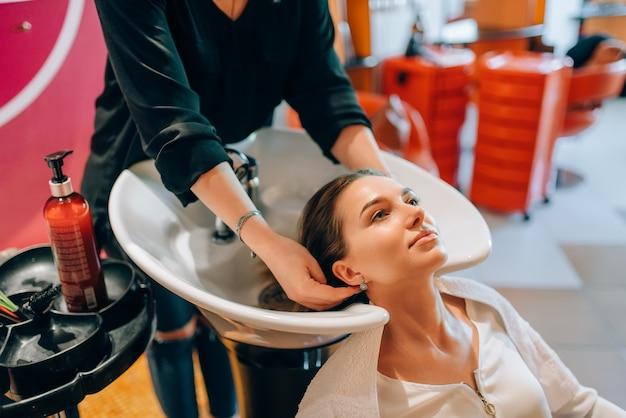 Il parrucchiere lava i capelli del cliente nel lavabo