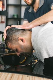 Il parrucchiere lava una testa maschile dopo un taglio di capelli dal barbiere.