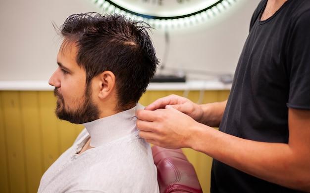 Il parrucchiere prepara il cliente per un taglio di capelli