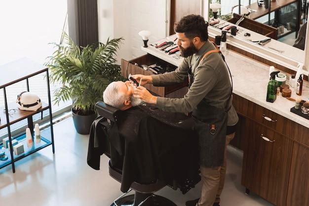 Il parrucchiere raddrizza la barba con il rasoio e la spazzola per capelli del cliente senior