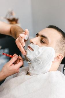 Il parrucchiere si rade la barba a un uomo con un rasoio dal barbiere