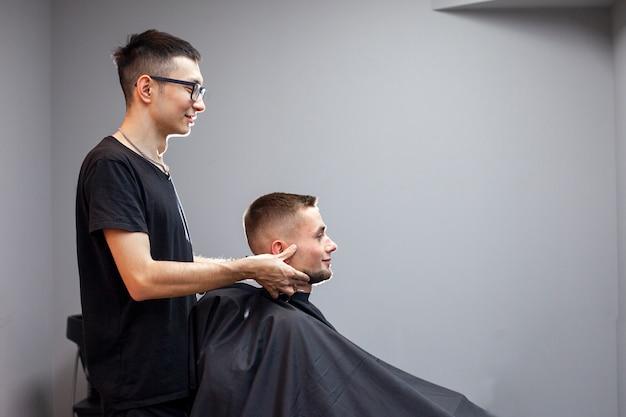 Il parrucchiere uzbeko taglia un giovane bel ragazzo in un barbiere, un cliente maschio si siede in un salone di bellezza e fa un taglio di capelli corto