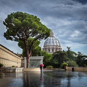 Il passante con un ombrello rosso cammina nel tempo piovoso lungo il viale vicino alla cattedrale di san pietro in vaticano.