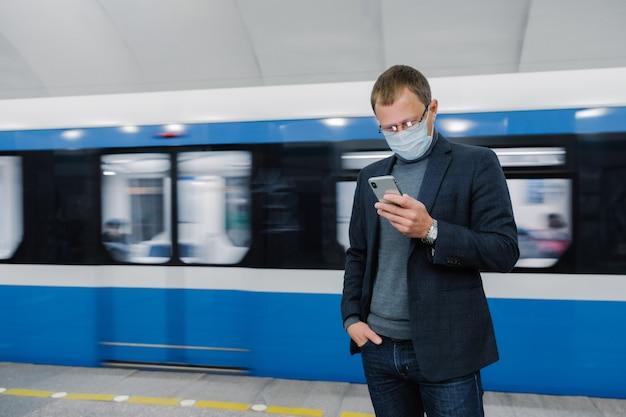 Il passeggero maschio indossa una maschera sul binario, aspetta il treno, fa la metropolitana, si concentra sul dispositivo smartphone, legge le notizie online. awereness virus in luogo pubblico. epidemia di coronavirus