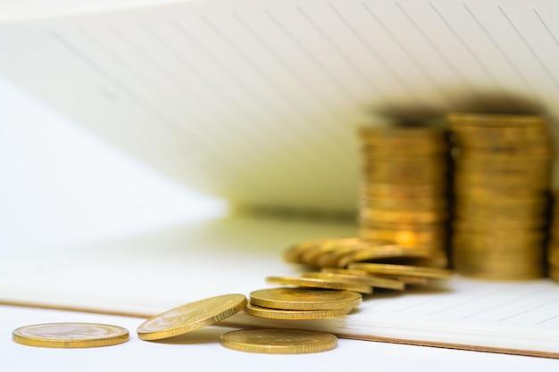 Il passo delle monete impila sul documento del taccuino con lo spazio della copia per aggiunge il testo