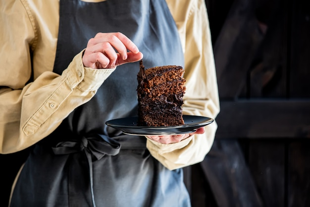 Il pasticcere in grembiule tiene la torta di cioccolato