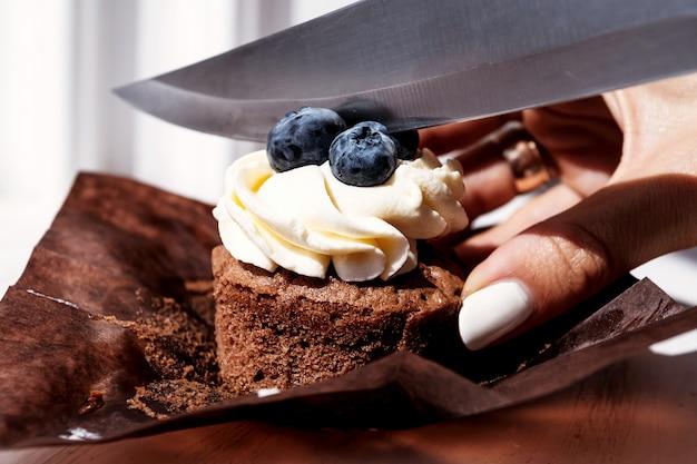 Il pasticcere taglia il dessert del bigné