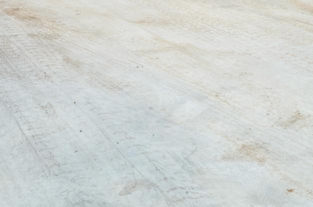 Il pavimento di calcestruzzo di superficie del primo piano con le piste della gomma ha strutturato il fondo