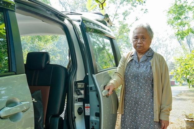 Il paziente anziano della donna anziana anziana o anziana della signora che si siede sulla sedia a rotelle prepara ottenere alla sua automobile