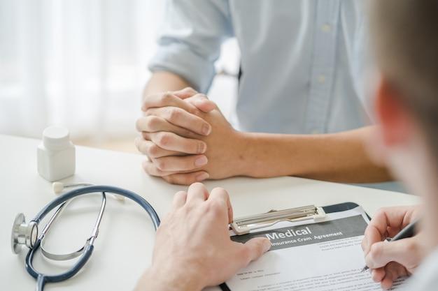 Il paziente d'ascolto del medico spiega il suo sintomo e le note alla cartella sanitaria.