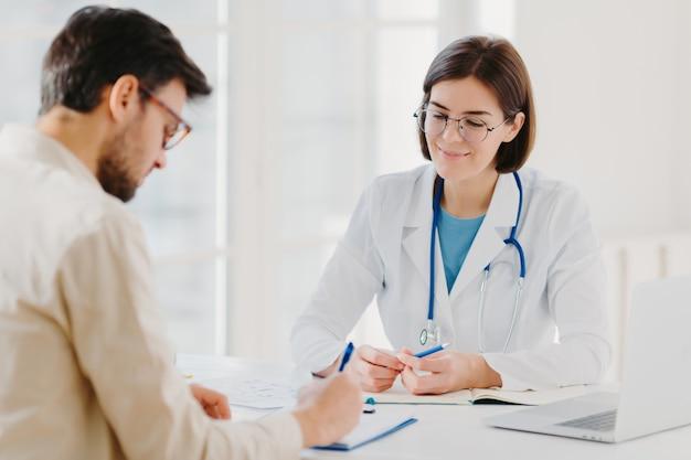 Il paziente maschio annota il modulo di domanda, ottiene consulenza e consigli sul trattamento domiciliare dal medico