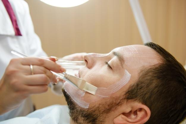 Il paziente maschio ottiene il trattamento facciale nella clinica di bellezza