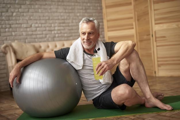 Il pensionato positivo beve l'acqua dopo l'allenamento.