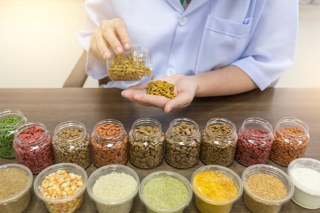 Il personale del laboratorio sta versando crocchette di cibo per gatti in mano per controllare la qualità.