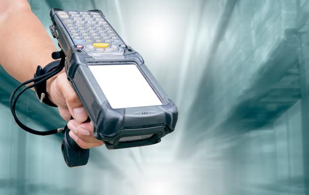 Il personale del magazzino è in possesso di scanner di codici a barre sullo sfondo del magazzino di sfocatura.