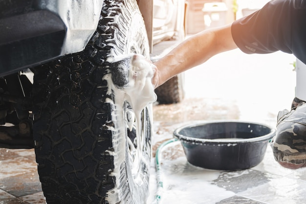 Il personale dell'autolavaggio sta usando una spugna inumidita con acqua e sapone per pulire le ruote dell'auto.