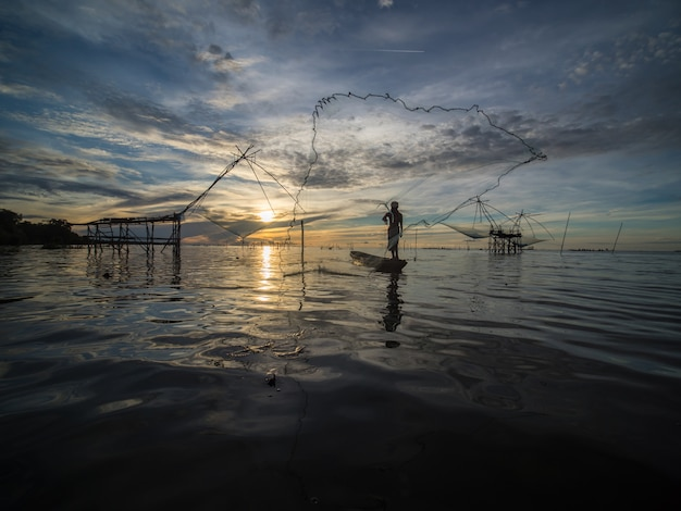 Il pescatore che getta la rete da pesca pesca il pesce che causa la spruzzata dell'acqua