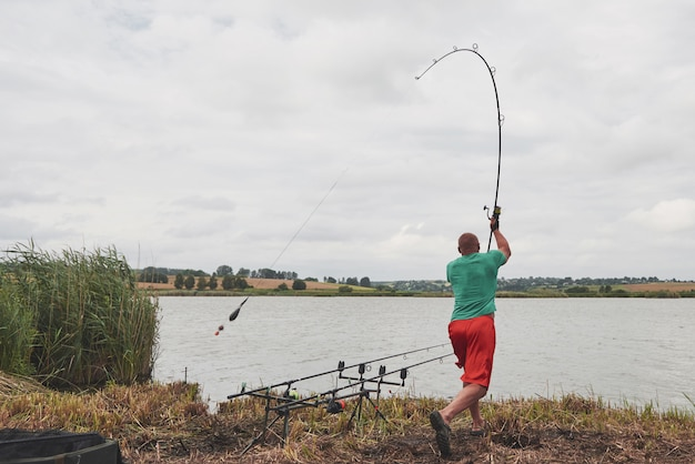 Il pescatore lancia un'esca con esca. oggi prenderà un grosso pesce. caccia e sport per hobby