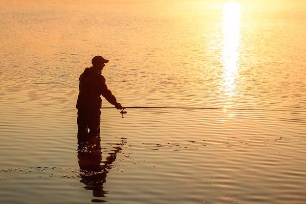 Il pescatore maschio all'alba sul lago pesca una canna da pesca vacanza di hobby di pesca